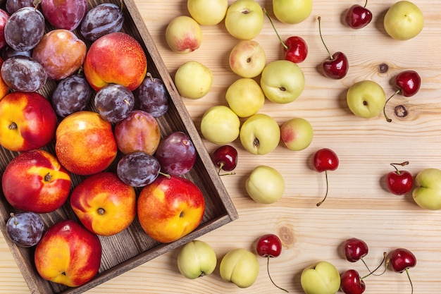 Nektarynki i śliwki w pudełku, brzoskwinie na stole.