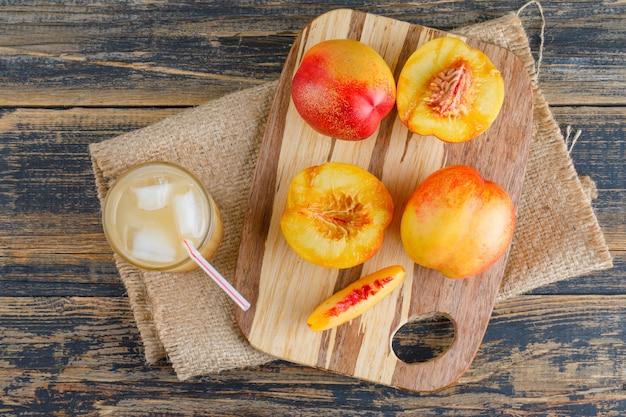 Nektarynki z deską do krojenia, sok na drewnie i kawałek worka