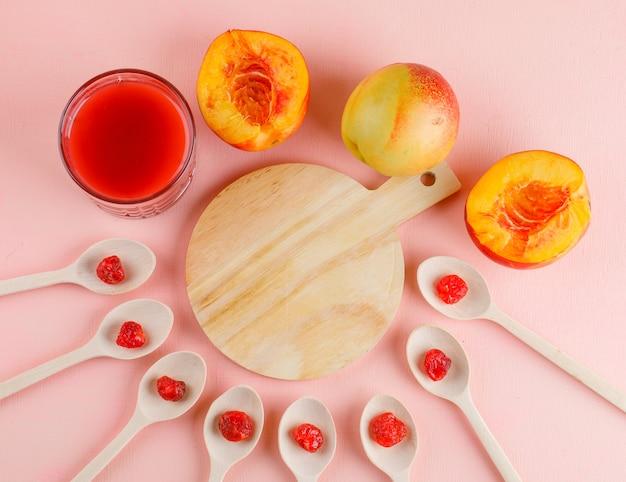 Nektarynki z sokiem, suszona wiśnia na różowo i stół do krojenia, układane na płasko.