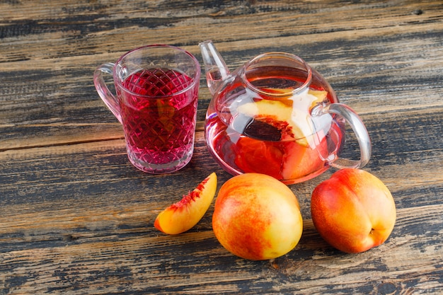 Nektarynki z zimnym napojem wysoki kąt widzenia na drewnianym stole