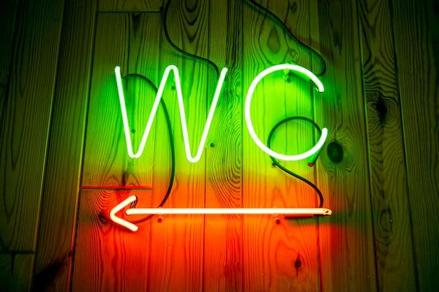 Neon wc na drewnianej ścianie. toaleta, toaleta z neonowym wskaźnikiem