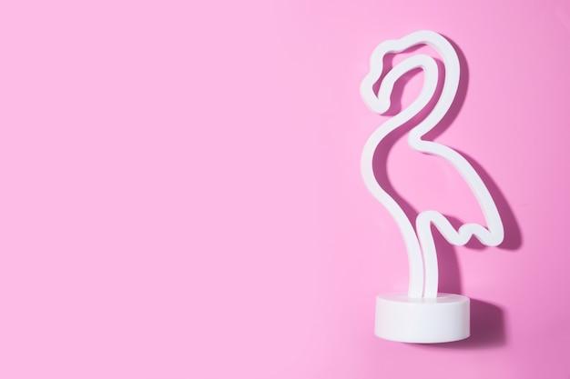 Neonowa różowa flamingowa lampa led na różowym tle.