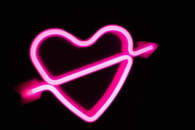 Neonowe różowe serce na czarno na białym tle. niewyraźne tło.