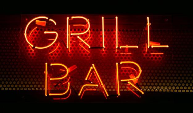 Neonowy napis grill bar w kolorze czerwonym na ciemnej ścianie. neonowy tekst na ścianie. projektowanie wnętrz