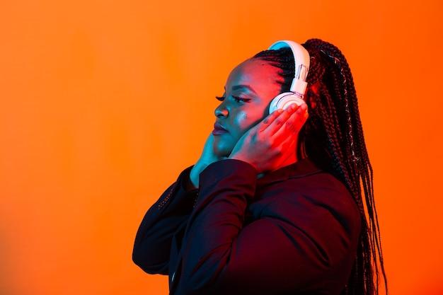 Neonowy portret młodej czarnej kobiety słuchać muzyki w słuchawkach.