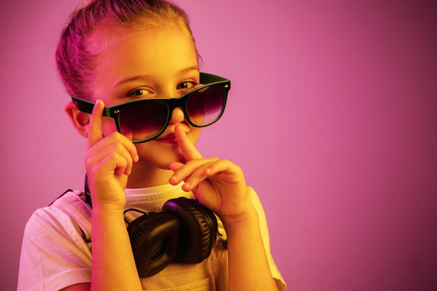 Neonowy portret młodej dziewczyny ze słuchawkami, słuchając muzyki i wzywając do ciszy.
