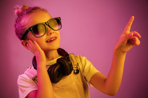 Neonowy portret młodej dziewczyny ze słuchawkami słuchania muzyki.