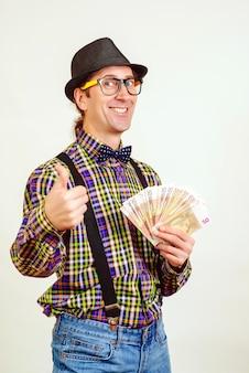 Nerd człowiek z fanem pieniędzy. mężczyzna gestykuluje kciuk w górę. sukces facet z gotówką. pojedynczo na białej ścianie.