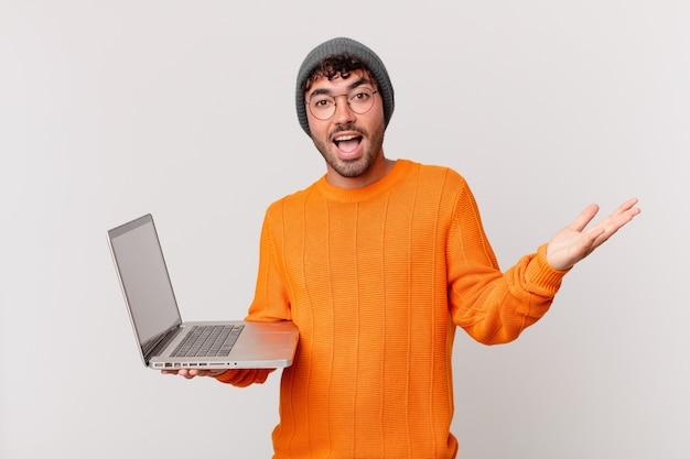 Nerd człowiek z komputerem czuje się szczęśliwy, podekscytowany, zaskoczony lub zszokowany, uśmiechnięty i zdumiony czymś niewiarygodnym