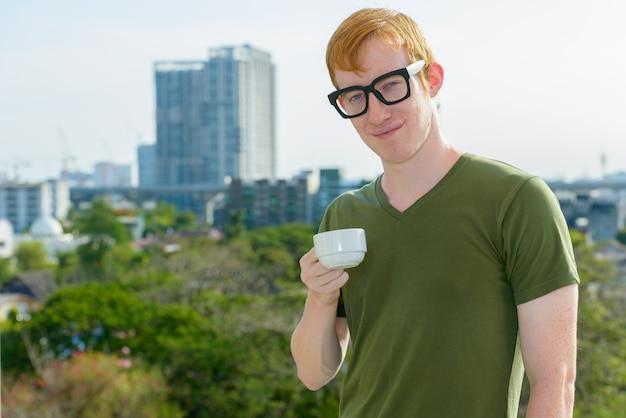 Nerd człowiek z rudymi włosami picia kawy z widokiem na miasto