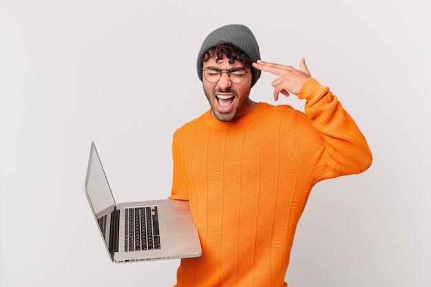 Nerd mężczyzna z komputerem wyglądający na niezadowolonego i zestresowanego, samobójczy gest wykonujący znak pistoletu ręką, wskazujący na głowę