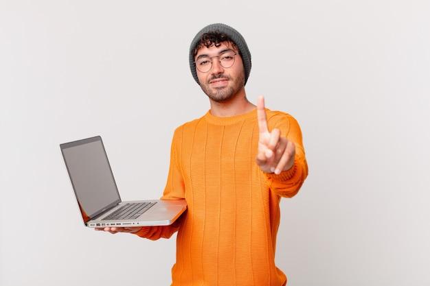 Nerd z komputerem uśmiechający się dumnie i pewnie, triumfalnie wykonując pozę numer jeden, czując się jak lider