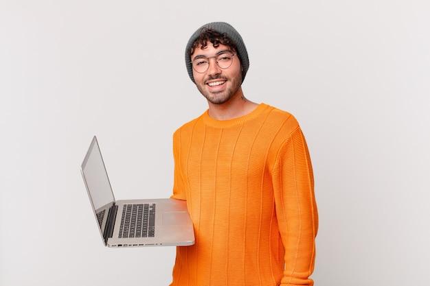 Nerd z komputerem wyglądający na szczęśliwego i mile zaskoczonego, podekscytowany z zafascynowanym i zszokowanym wyrazem twarzy