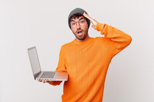 Nerd z komputerem wyglądający na szczęśliwego, zdziwionego i zdziwionego, uśmiechnięty i realizujący niesamowite i niewiarygodnie dobre wieści
