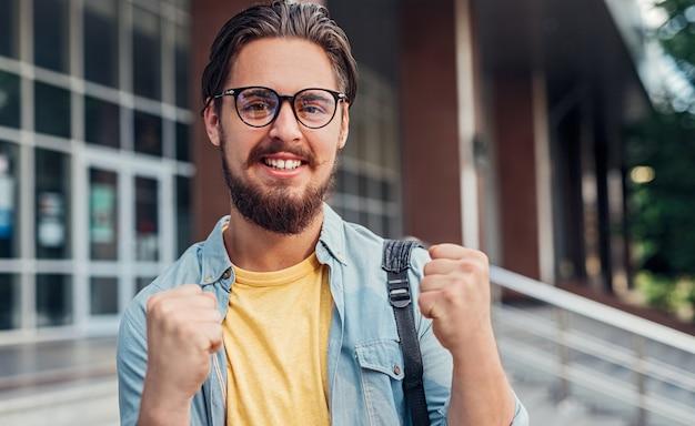 Nerdowaty student raduje się po zdaniu egzaminu