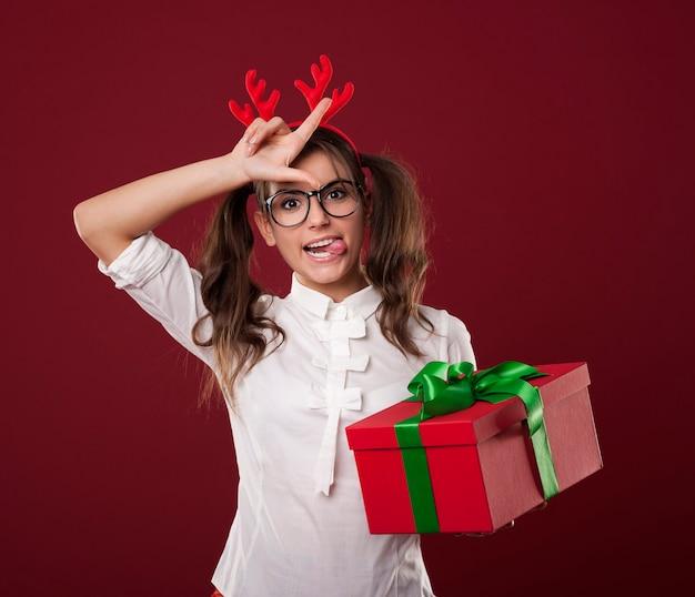 Nerdy kobieta z prezentem świątecznym pokazuje znak przegranego