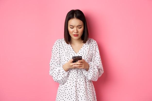 Nerwowa i zaniepokojona azjatka czytająca wiadomość na smartfonie, wyglądająca na zmartwioną, stojąca w sukience na różowym tle.