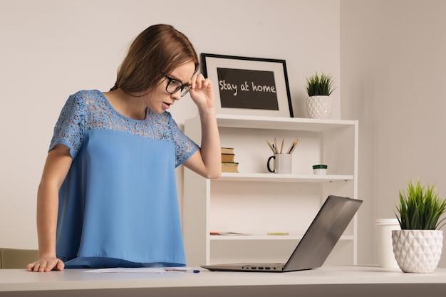 Nerwowa młoda bizneswoman stojąca w białym pokoju biurowym - obraz