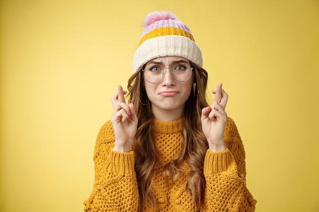 Nerwowa niepewna niepewna urocza nerd dziewczyna studentka uniwersytetu w okularach dąsająca się płacz, skomlenie zmartwiony krzyż palce powodzenia modląc się marzenie się spełniło stojąc intensywne żółte tło