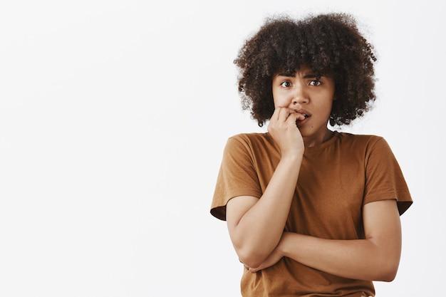 Nerwowa panikująca ciemnoskóra kobieta z fryzurą w stylu afro gryzie paznokcie i patrzy zmartwiona, jakby czekała na złe rzeczy