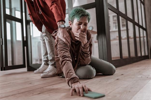 Nerwowy argument. zielonowłosa dziewczyna siedzi na podłodze i bierze smartfona po poważnej kłótni nerwowej
