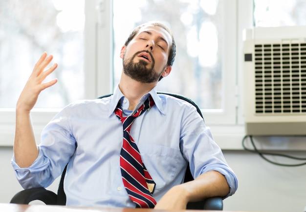 Nerwowy biznesmen pracuje w bardzo gorącym biurze, jest pocenie się i rozluźniający jego krawat