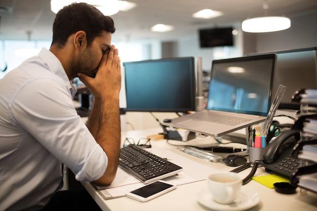 Nerwowy biznesmen siedzi w biurze