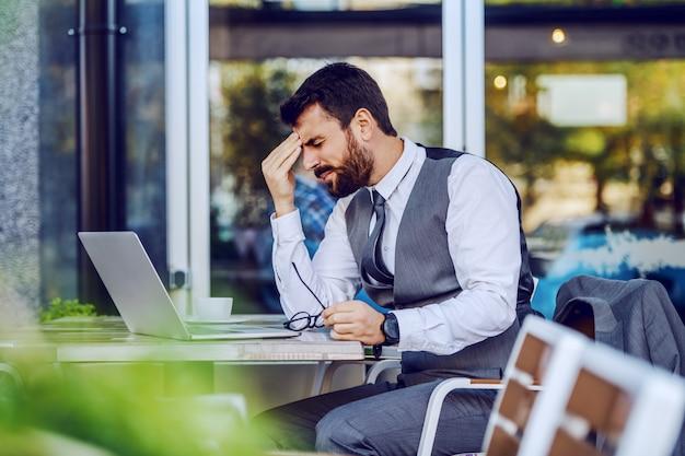 Nerwowy kaukaski przystojny brodaty biznesmen w garniturze siedzi w kawiarni i trzymając głowę. na stole laptop, kawa i okulary. kłopoty w pracy.
