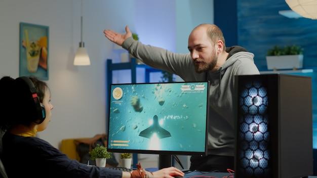Nerwowy mężczyzna krzyczy na kobietę, która gra w kosmiczną strzelankę na potężnym komputerze rgb i rywalizuje online. pro cyber z zestawem słuchawkowym występującym podczas wirtualnego turnieju