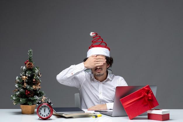 Nerwowy młody biznesmen z zabawnym czapką świętego mikołaja świętuje boże narodzenie i zamyka oczy w biurze na ciemnym tle