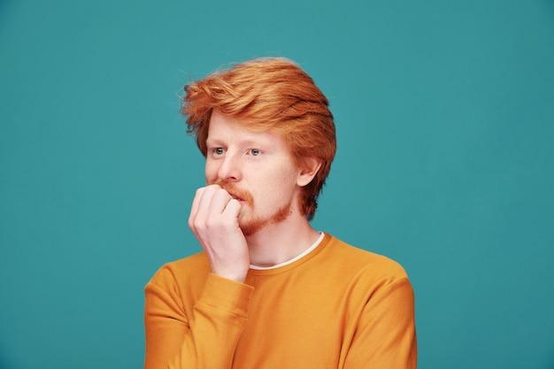 Nerwowy młody rudy mężczyzna w pomarańczowym swetrze gryzie paznokcie na niebiesko