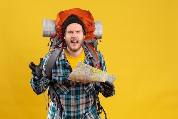 Nerwowy młody turysta w skórzanych rękawiczkach i plecaku trzymającym mapę