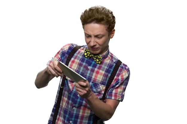 Nerwowy nastoletni gracz gra na swoim smartfonie. chłopiec gra w grę z wyrazistym wyrazem twarzy gniewu. na białym tle.