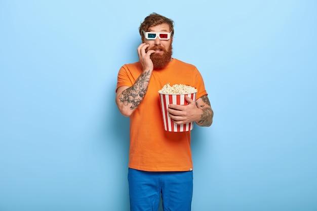 Nerwowy przerażony brodaty rudy mężczyzna pozuje z popcornem