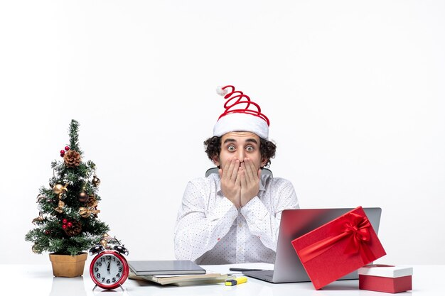 Nerwowy zszokowany młody biznesmen z zabawnym czapką świętego mikołaja świętuje boże narodzenie w biurze na białym tle
