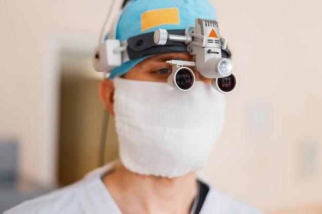 Neurochirurg w białej masce, w specjalnym ubraniu medycznym, w lupach z lupą lornetkową, jest w szpitalu. okulary chirurgiczne. wyposażenie medyczne