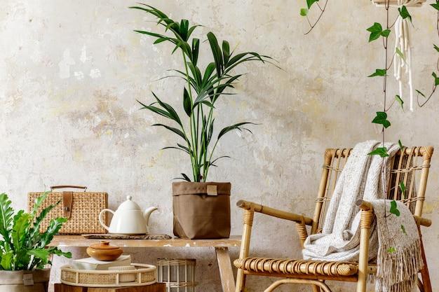 Neutralna kompozycja wnętrza salonu z rattanowym fotelem, drewnianą ławką, mnóstwem tropikalnych roślin w designerskich donicach, dekoracją i eleganckimi dodatkami osobistymi w stylowym wystroju domu.