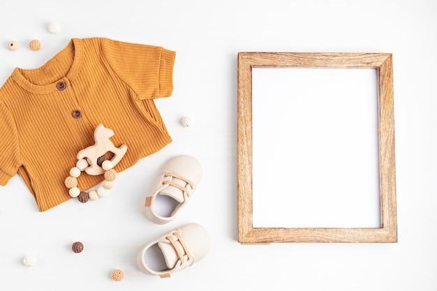 Neutralna pod względem płci ubranka dla niemowląt, akcesoria i pusta ramka. ubrania z bawełny organicznej, moda noworodkowa, branding, pomysł na mały biznes. płaski układanie, widok z góry