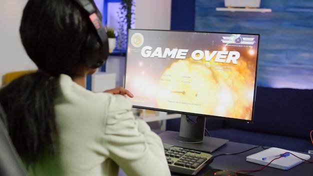 Nevous pro african cyber przegrywająca gra wideo, koniec gry dla kobiety grającej w kosmiczne strzelanki online z zestawem słuchawkowym