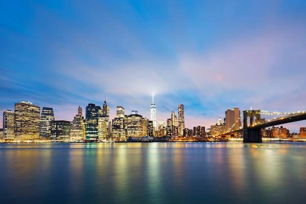 New york city manhattan midtown o zmierzchu z drapaczami chmur oświetlonymi nad wschodnią rzeką