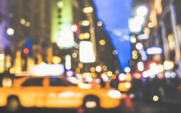 New york city streszczenie godziny szczytu - nieostry żółty samochód taksówką i korek uliczny na 5. alei w centrum manhattanu
