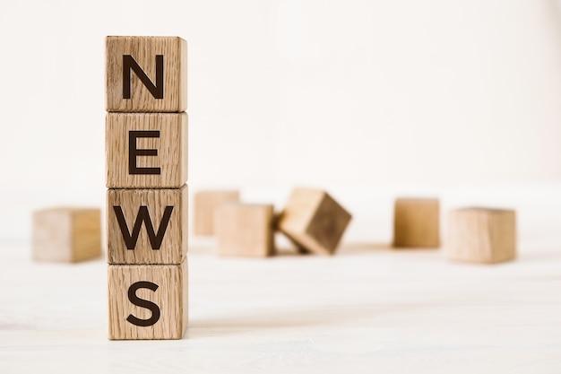 News słowo wykonane z drewnianych kostek na jasnym tle z rozmytymi kostkami.