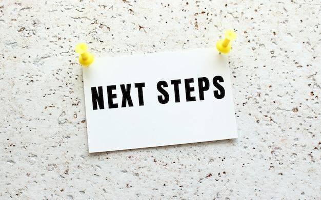 Next steps jest napisane na karcie przyczepionej do białej, teksturowanej ściany za pomocą przycisku. przypomnienie o biurze. pomysł na biznes.
