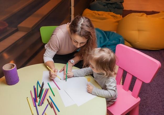 Niania uczy małą dziewczynkę, jak rysować kredkami, siedząc przy stole w centrum rozrywki dla dzieci