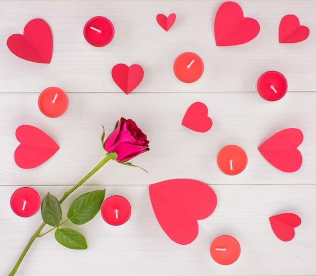 Nić czerwone róże, papierowi serca i świeczki na białym drewnianym stole ,.
