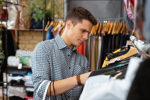 Nic interesującego. spokojny, poważny młody człowiek w zamyśleniu szuka nowych ubrań w sklepie z ubraniami i nie widzi nic ciekawego