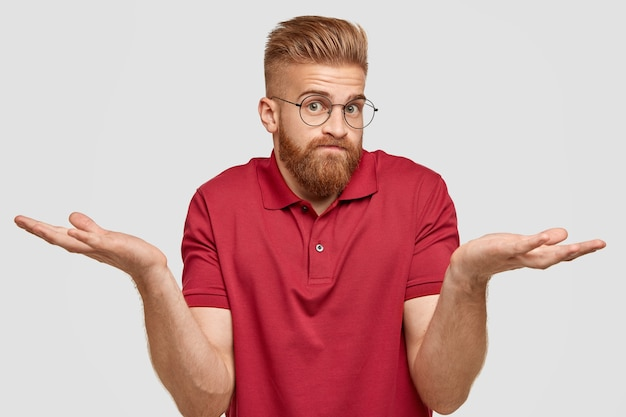 Nic nie wiem. przystojny stylowy hipster z gęstą rudą brodą, rozpościera dłonie z pytającą miną
