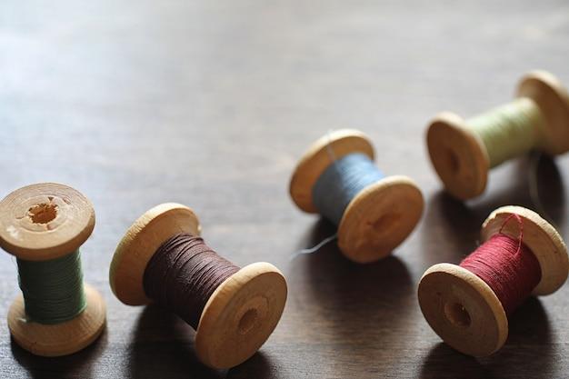 Nici do szycia na drewnianym tle. zestaw nici na szpulkach w stylu retro. zabytkowe dodatki do szycia na stole