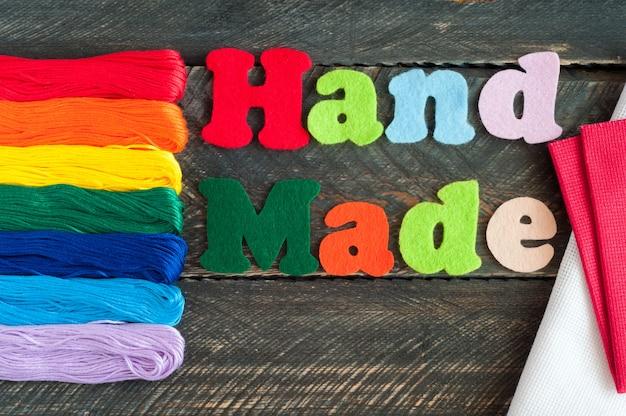 Nici nici do haftu, płótna i napisu ręcznie robione z filcu na starym drewnianym tle