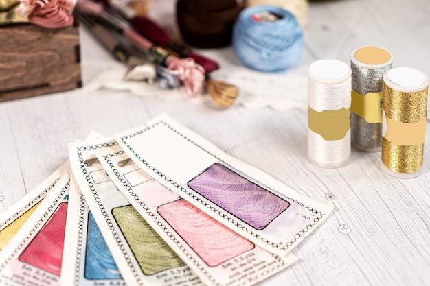 Nici w rolkach. kolorowe szpulki do haftowania akcesoriów hobby i kreatywności. tło
